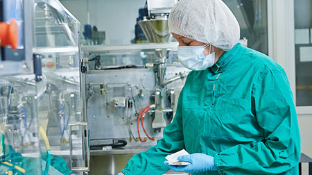 Person working in the medical equipment industry, wearing personal protections.
