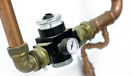 A pressure regulator installed on a compressed air system.